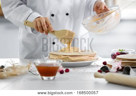 Cooking concept. Professional confectioner making delicious cake, closeup