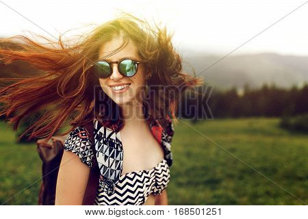 Stylish Woman Traveler With Fashionable Sunglasses And Windy Hair Smiling And Having Fun On Top Of M