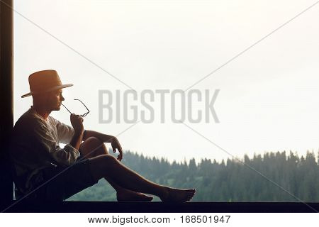 Man Sitting Relaxing And Thinking With Glasses In Hand On Porch Of Wooden House Looking At Mountains
