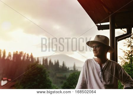 Hipster Man Standing On Porch Of Wooden House  Looking At Mountains In Evening Sunset, Calm Relaxing