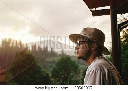 Hipster Man On Porch Of Wooden House  Looking At Mountains In Evening Sunset, Calm Relaxing Moment,