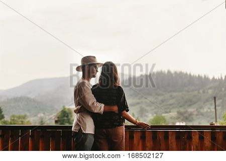 Hipster Couple Hugging On Porch Of Wooden House Looking At Mountains In Evening Sunset, Romantic Mom
