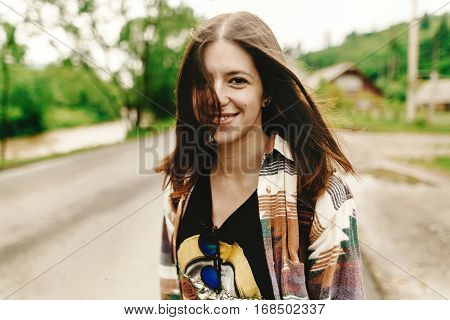 Stylish Hipster Woman Smiling And Relaxing, Calm Mood In Sunny  In Summer Mountains Road, Travel Con