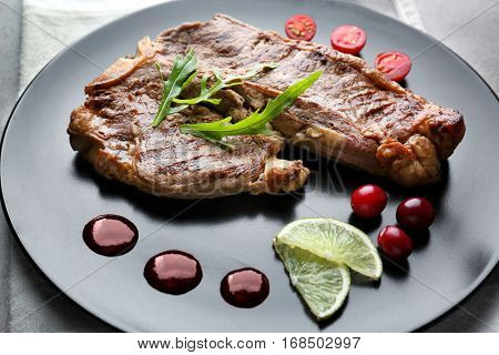 Tasty grilled steak with cranberry sauce, lime and arugula on plate
