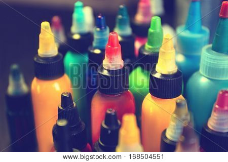 Multiple bottles with colorful inks for tattoo, close up view