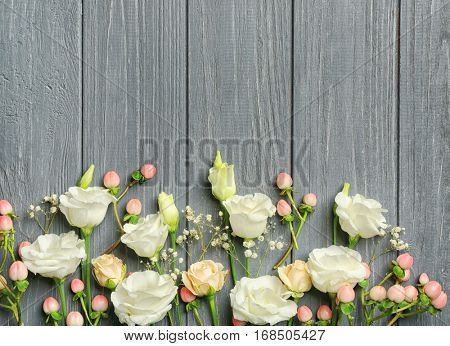 Hypericum, eustoma and roses on gray wooden background