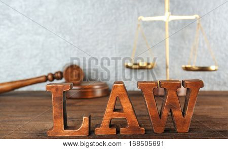 Word LAW made of wooden letters on table, closeup
