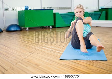 Fit blonde doing sitting up on mat in fitness studio