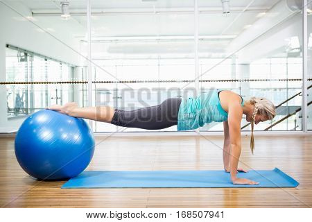 Fit blonde planking on mat with exercise ball in fitness studio