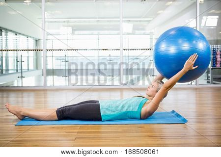 Fit blonde on mat holding fitness ball in the studio