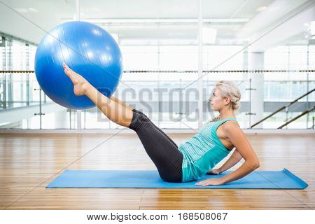 Fit blonde on mat holding with legs fitness ball in the studio