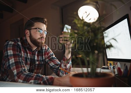 Portrait of a young concentrated attractive man using mobile phone while working with computer in the office