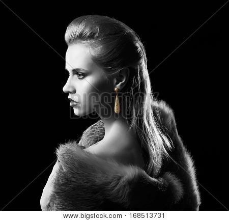 Young woman with golden earring on black background