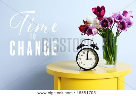 Alarm clock with flowers on yellow table. Text TIME TO CHANGE on blue wall background