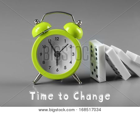 Dominoes with alarm clock and TIME TO CHANGE on gray background