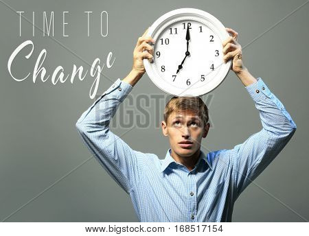Young man with clock and text TIME TO CHANGE on gray background