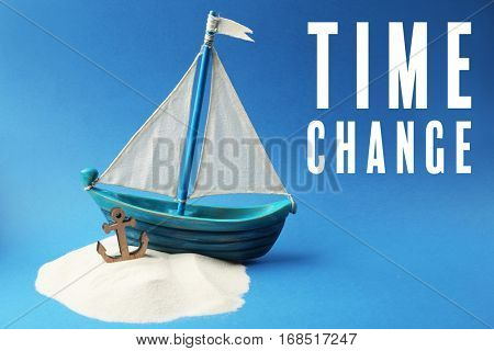 Wooden boat with anchor, sand and text TIME CHANGE on blue background