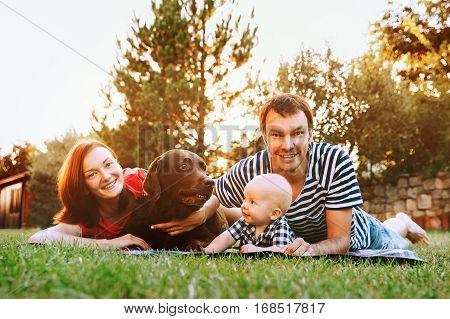 Family lying on the grass in the park together on a spring summer day. Mother Father and Cute Little Baby Child at stylish casual clothing on nature with dog. Parents and activity with baby outdoors.