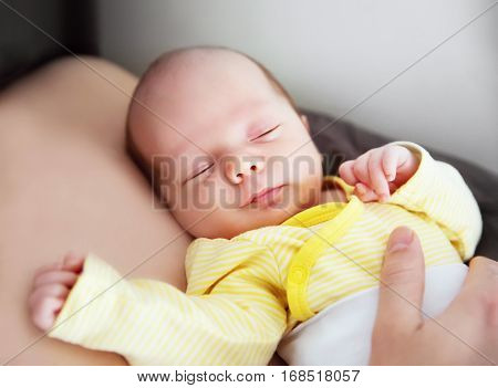 Newborn baby sleeping peacefully on father's chest