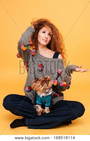Portrait of a pretty red hair woman holding copy space on her palm while sitting with dog isolated on orange background