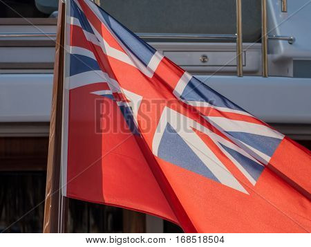 in the port of bareclona in spain are yachts. they fly the flag of the cayman islands