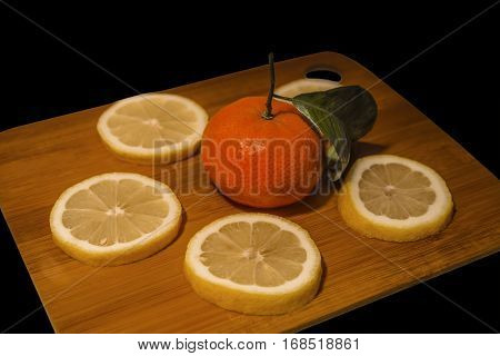 Mandarin surrounded by lemon washers lying on a wooden board