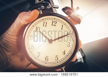 Time is Running Out. Large Classic Alarm Clock in a Hand.