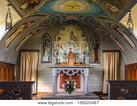 Orkneys Scotland - June 5 2012: Italian Chapel on Lamb Holm Island. Chancel and altar with bright sharp and detailed wall and ceiling paintings featuring the madonna with child angels and more