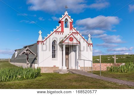 Orkneys Scotland - June 5 2012: The entire building entrance and front facade of the white and maroon painted Italian Chapel on Lamb Holm Island. Green lawn in front against deep blue sky.