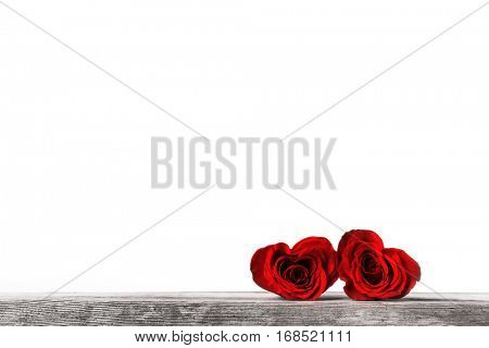 Two heart shaped red roses on wooden background, Valentines day
