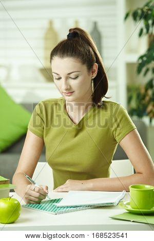 Student girl sitting at desk at home, learning looking down.