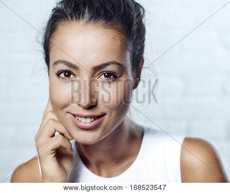 Closeup portrait of beautiful young woman smiling, looking at camera.