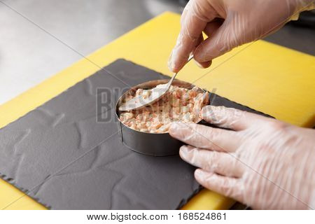Chef is serving appetizer on slate plate with metal ring, commercial kitchen