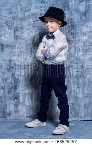 Cute little boy in elegant clothes and a hat. Be like daddy. Kid's fashion. Full length portrait.