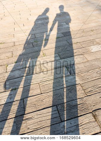 Shadow of lovers on floor, shadow of Man holding hand woman