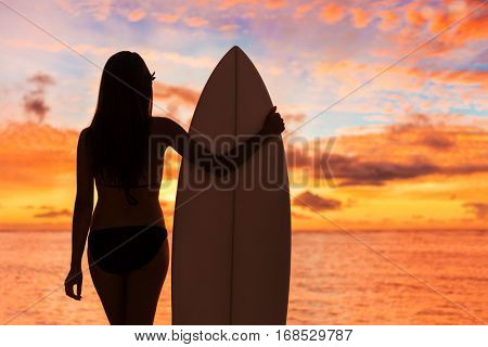 Beach sunset sexy surfer woman surfing lifestyle relaxing holding surfboard looking at ocean waves for surf. Active healthy living silhouette of sports athlete standing in colorful sky.