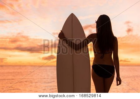 Beach sunset sexy surfer woman surfing lifestyle holding surfboard looking at ocean waves for surf. Active silhouette of sports athlete girl in bikini standing in colorful sky.