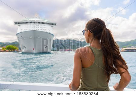 Woman tourist on outdoor shore excursion looking at cruise ship boat docked at port of call harbour in Caribbean destination. Tropical summer travel, tourism vacation.