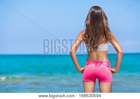 Beautiful fitness model standing against ocean background with fit body confident. Sportswear weight loss happy body active lifestyle concept. Summer living woman. poster