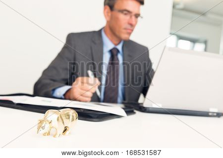 manager sitting at his desk, working on his laptop. focus is on the bear figurine in the foreground, symbolizing failure.