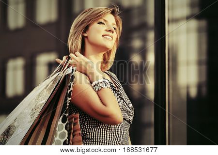 Happy young woman with shopping bags walking on city street  Stylish fashion model outdoor