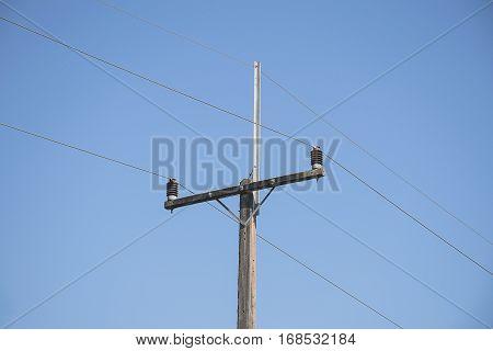 Concrete electric pole against blue clear sky.