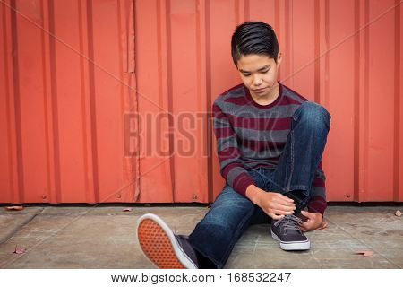 Lonely sad Asian boy sitting back against a metal wall while gazing down.