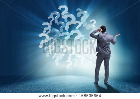 Businessman in uncertainty concept with question marks