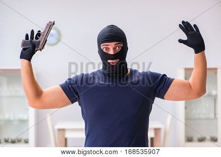 Robber wearing balaclava stealing valuable things