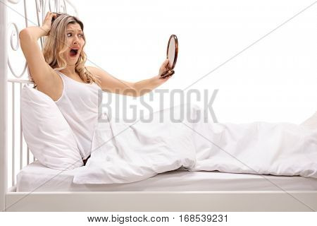 Shocked woman lying in bed and looking at a mirror isolated on white background