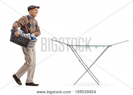 Full length portrait of a senior holding a laundry basket full of clothes and walking towards a clothing rack dryer isolated on white background