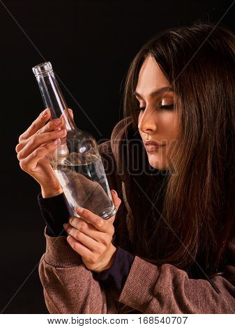 Woman alcoholism is social problem. Female drinking is cause of poor health. She drinking alcohol in bad mood. Black background as a symbol of mourning.