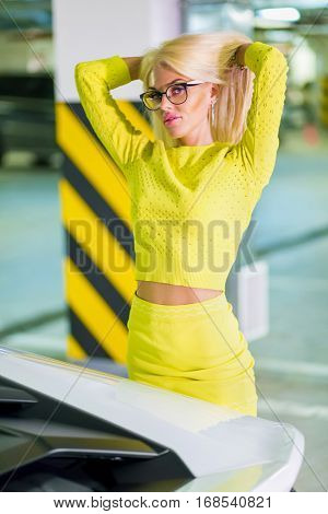 Young woman in yellow suit rearrange hair standing near white car at underground parking.