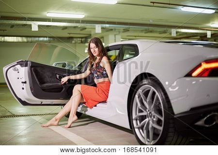 Young smiling barefoot woman sits on driver seat of modern white car at underground parking.